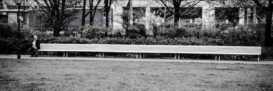 Mann sitzt ganz allein auf einer ganz langen Bank im Park