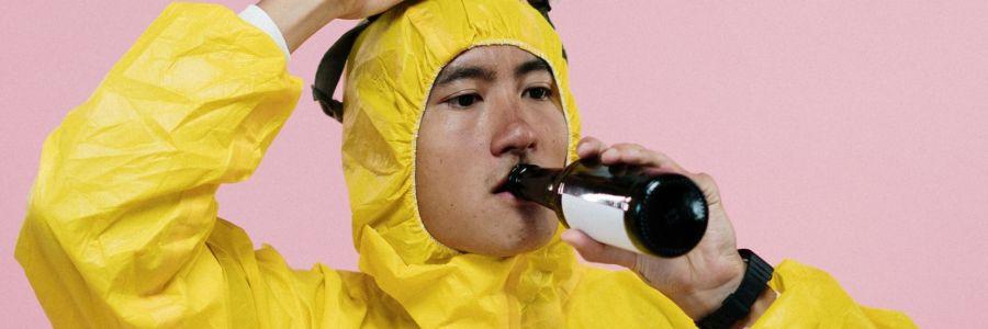 Mann in gelbem Overall trinkt ein Bier.