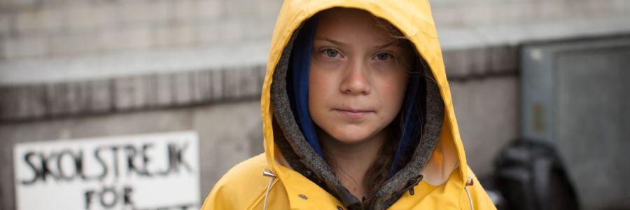 Greta Thunberg steht in einem gelben Regenmantel vor ihrem Protestschild.