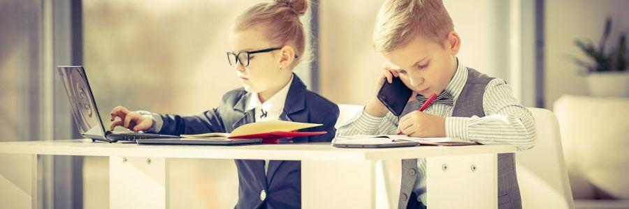 Zwei Kinder im Businesslook mit Telefon und Laptop am Schreibtisch.