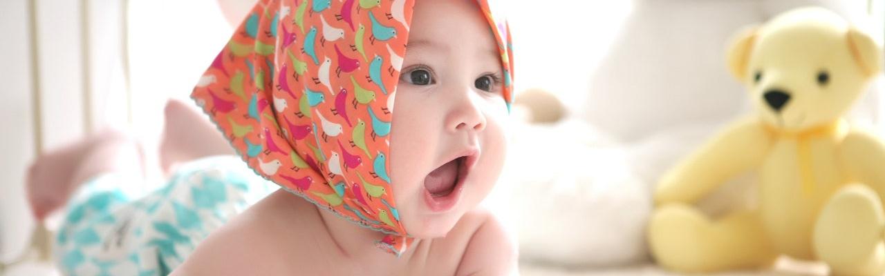 Baby mit Kopftuch auf Spieledecke.