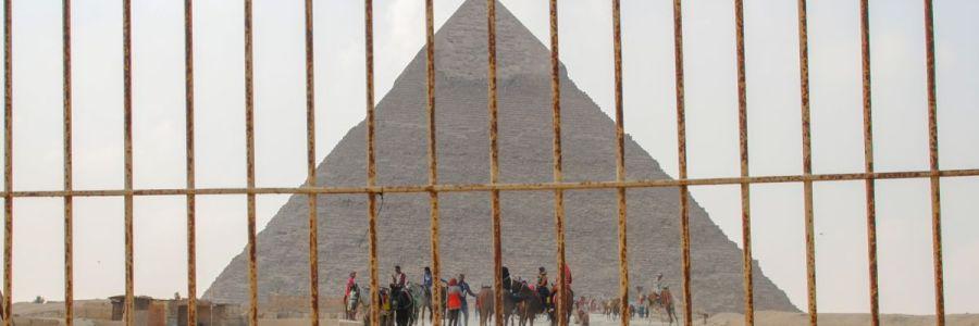 Blick auf eine Pyramide in Gizeh durch einen metallenen Gitterzaun.