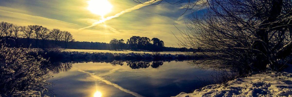 Winterlandschaft mit Fluss, Wiese, Sonne, blauem Himmel und Kondenzstreifen
