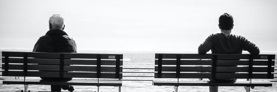Zwei Männer sitzen jeweils auf einer Bank und starren in die Ferne.