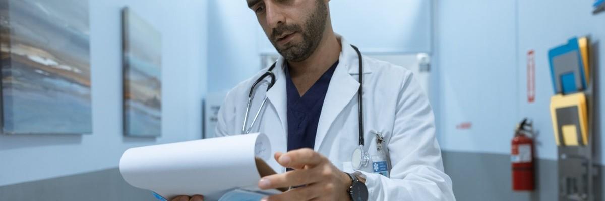 Ein Arzt steht im Gang eines Krankenhauses und schaut auf ein Klemmbrett.