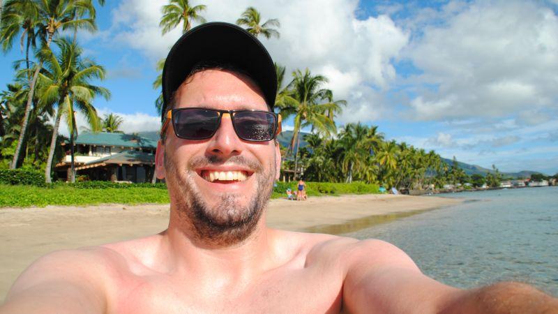 Stefan Kübler am Strand von Maui mit Palmen im Hintergrund.