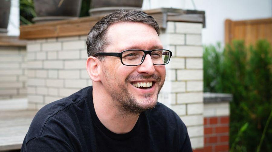 Stefan Kübler sitzt auf der Terrasse und lächelt.