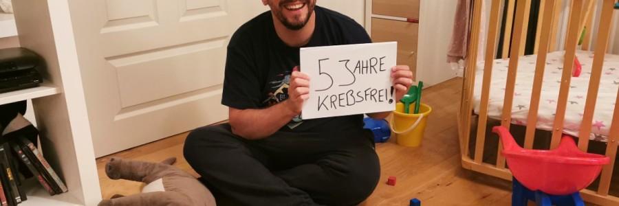 Stefan Kübler sitzt im Wohnzimmer inmitten von Spielzeug und feiert fünf Jahre krebsfrei.